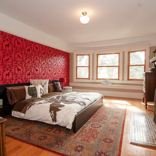 Example of an eclectic medium tone wood floor bedroom design in Portland with red walls and a standard fireplace