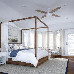 ニューヨークのビーチスタイルのおしゃれな主寝室 (グレーの壁、壁紙、茶色い床、無垢フローリング、三角天井) のインテリア