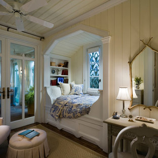 Photo of a beach style bedroom in New York with yellow walls and dark hardwood floors.
