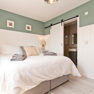 Photo of a medium sized beach style bedroom in Dorset with green walls and grey floors.