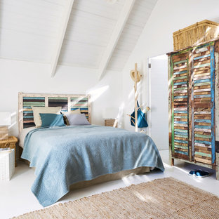 Design ideas for a mid-sized beach style master bedroom in London with white walls and white floor.