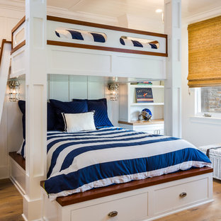 Photo of a mid-sized beach style loft-style bedroom in San Diego with white walls, light hardwood floors and grey floor.