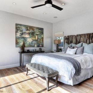 オレンジカウンティのビーチスタイルのおしゃれな寝室 (グレーの壁、無垢フローリング) のインテリア