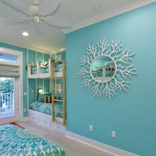 Diseño de habitación de invitados costera, de tamaño medio, con paredes azules y suelo de madera clara