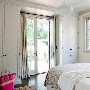Exempel på ett klassiskt sovrum, med vita väggar och mörkt trägolv