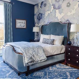 Diseño de dormitorio principal, clásico, de tamaño medio, con paredes azules, suelo de madera en tonos medios, chimenea tradicional, marco de chimenea de baldosas y/o azulejos y suelo marrón