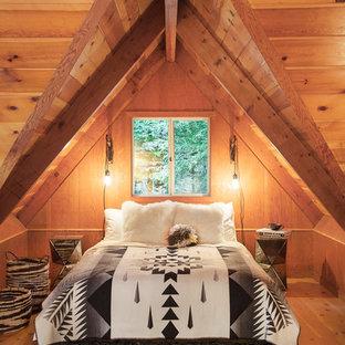 Modelo de dormitorio tipo loft, rural, de tamaño medio, con suelo de madera en tonos medios, paredes marrones y suelo marrón