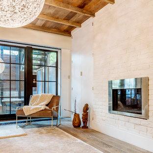 На фото: хозяйская спальня в современном стиле с белыми стенами, темным паркетным полом, стандартным камином, фасадом камина из кирпича и белым полом с