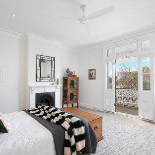 Inspiration for a large transitional master bedroom in Sydney with white walls, carpet, a standard fireplace, a plaster fireplace surround and grey floor.