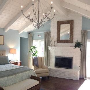 Inspiration för ett stort vintage huvudsovrum, med blå väggar, mörkt trägolv, en standard öppen spis, en spiselkrans i tegelsten och brunt golv