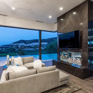 На фото: класса люкс большие хозяйские спальни в современном стиле с фасадом камина из плитки, белыми стенами, темным паркетным полом, горизонтальным камином и коричневым полом