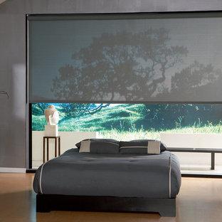 Cette image montre une grand chambre parentale design avec un mur gris, sol en stratifié, aucune cheminée et un sol orange.