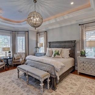 Modelo de dormitorio principal, tradicional, grande, sin chimenea, con paredes grises, suelo de madera en tonos medios y suelo marrón