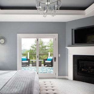 Foto de dormitorio principal, de estilo americano, grande, con paredes grises, moqueta, chimenea de esquina, marco de chimenea de madera y suelo gris