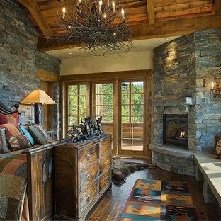 Ejemplo de dormitorio principal, rústico, grande, con paredes multicolor, suelo de madera oscura, chimenea de esquina, marco de chimenea de piedra y suelo marrón