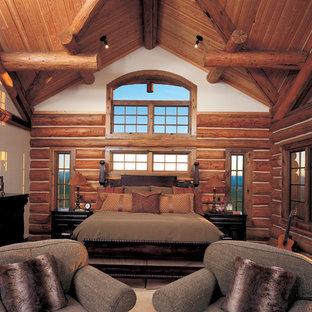 Ejemplo de dormitorio principal, rústico, grande, con paredes blancas, moqueta, chimenea tradicional, marco de chimenea de piedra y suelo beige