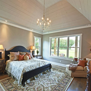 Example of a cottage master medium tone wood floor and brown floor bedroom design in Other with beige walls and no fireplace