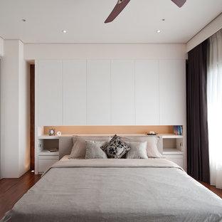 Foto de dormitorio actual, sin chimenea, con paredes blancas y suelo de madera en tonos medios