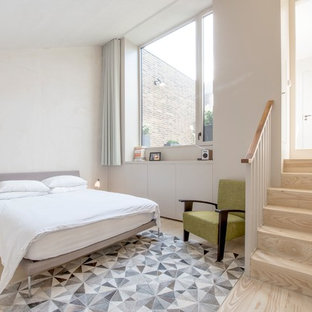 This is an example of a scandinavian guest bedroom in London with white walls, light hardwood flooring and beige floors.