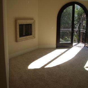 Неиссякаемый источник вдохновения для домашнего уюта: хозяйская спальня среднего размера в средиземноморском стиле с бежевыми стенами, бетонным полом, горизонтальным камином, фасадом камина из дерева и разноцветным полом