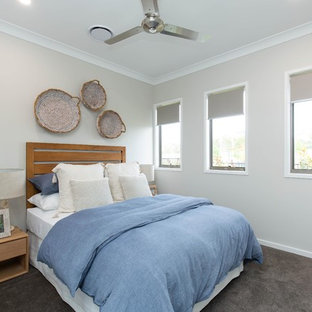 This is an example of a mid-sized beach style guest bedroom in Sunshine Coast with carpet, grey floor and beige walls.