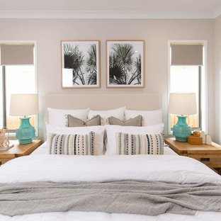 Mid-sized beach style master bedroom in Brisbane with carpet, grey floor and beige walls.