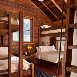 Esempio di una camera degli ospiti con pareti marroni e pavimento in legno massello medio