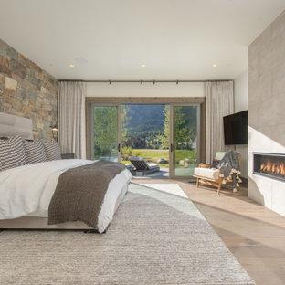 Ejemplo de dormitorio principal, rural, con suelo de madera clara, chimenea tradicional, marco de chimenea de hormigón y suelo marrón