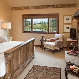 Imagen de dormitorio principal, rural, con moqueta, chimenea tradicional y marco de chimenea de piedra