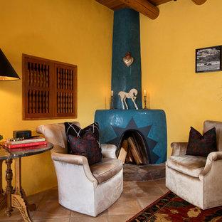 アルバカーキの中サイズのエクレクティックスタイルのおしゃれな主寝室 (黄色い壁、磁器タイルの床、コーナー設置型暖炉、漆喰の暖炉まわり) のインテリア