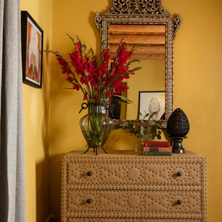 アルバカーキの中くらいのエクレクティックスタイルのおしゃれな主寝室 (黄色い壁、磁器タイルの床、コーナー設置型暖炉、漆喰の暖炉まわり) のレイアウト