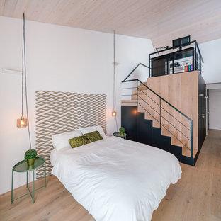 Foto de dormitorio principal, actual, de tamaño medio, con paredes blancas, suelo de madera en tonos medios y suelo marrón