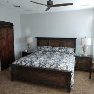 ボイシの中サイズのトラディショナルスタイルのおしゃれな主寝室 (グレーの壁、カーペット敷き、コーナー設置型暖炉、レンガの暖炉まわり、茶色い床) のインテリア