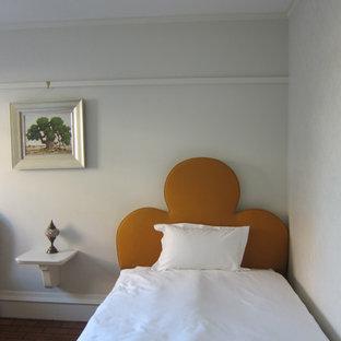 Immagine di una piccola camera degli ospiti tradizionale con pavimento in mattoni e pareti grigie