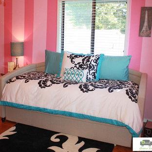 Klassisk inredning av ett mellanstort sovrum, med rosa väggar och mellanmörkt trägolv