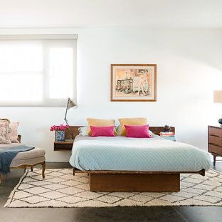 Example of a large eclectic master concrete floor bedroom design in Los Angeles with white walls and no fireplace