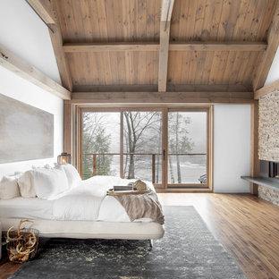 На фото: спальня в стиле рустика с белыми стенами, паркетным полом среднего тона, горизонтальным камином и коричневым полом с