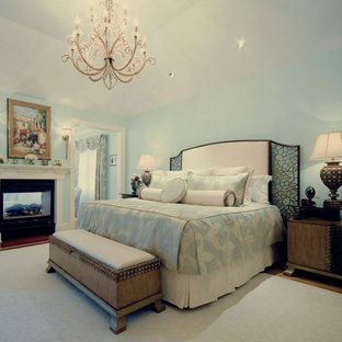 Inspiration for a large timeless master light wood floor bedroom remodel in New York with a two-sided fireplace and a metal fireplace