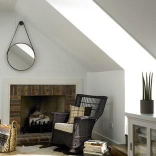 Ejemplo de habitación de invitados de estilo de casa de campo, de tamaño medio, con paredes blancas, suelo de madera en tonos medios, chimenea tradicional y marco de chimenea de ladrillo