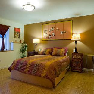 Diseño de dormitorio contemporáneo, sin chimenea, con paredes marrones, suelo de madera en tonos medios y suelo amarillo