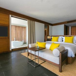 Imagen de dormitorio principal, tropical, sin chimenea, con paredes blancas y suelo negro