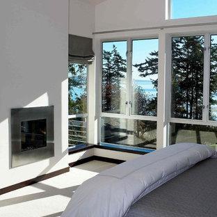 Modelo de dormitorio principal, moderno, de tamaño medio, con paredes blancas, moqueta, chimenea tradicional, marco de chimenea de metal y suelo blanco