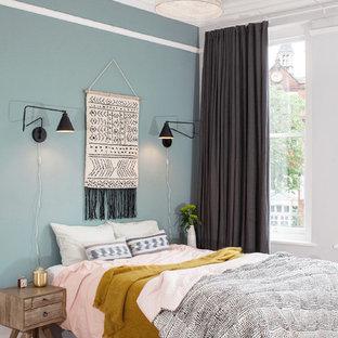 Esempio di una camera da letto nordica di medie dimensioni con pareti blu, parquet chiaro e pavimento beige