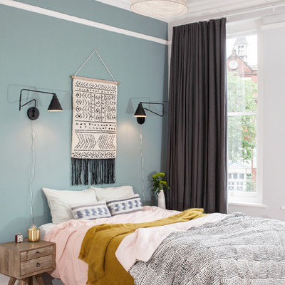Example of a mid-sized danish light wood floor and beige floor bedroom design in London with blue walls