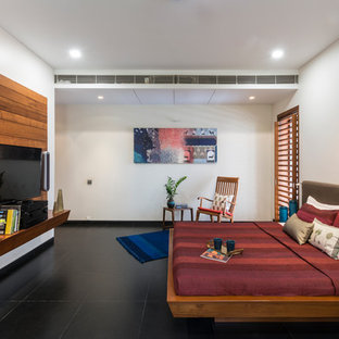 This is an example of a contemporary master bedroom in Other with white walls, black floor and concrete floors.