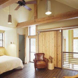 Diseño de dormitorio rústico con paredes beige y suelo de madera en tonos medios