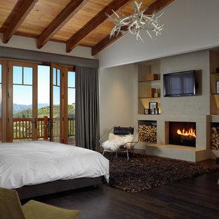 Стильный дизайн: гостевая спальня среднего размера в стиле рустика с белыми стенами, темным паркетным полом, стандартным камином, фасадом камина из штукатурки и коричневым полом - последний тренд