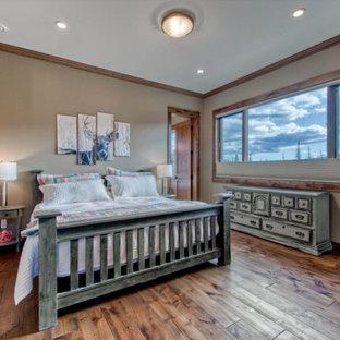 Inspiration pour une chambre parentale chalet de taille moyenne avec un mur beige, un sol en bois brun, une cheminée standard, un manteau de cheminée en pierre de parement et un sol marron.