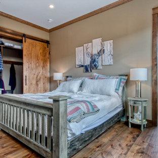 Exemple d'une chambre parentale montagne de taille moyenne avec un mur beige, un sol en bois brun, une cheminée standard, un manteau de cheminée en pierre de parement et un sol marron.