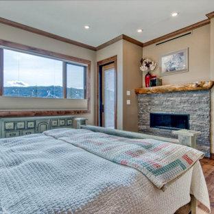 Modelo de dormitorio principal, rural, de tamaño medio, con paredes beige, suelo de madera en tonos medios, chimenea tradicional y suelo marrón